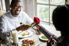 Homem romântico que dá uma Rosa à mulher em uma data fotografia de stock royalty free