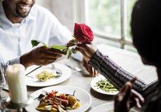 Homem romântico que dá uma Rosa à mulher em uma data imagens de stock