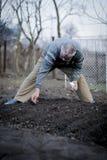 Homem romeno idoso que trabalha sua terra em uma maneira tradicional com mãos vazias imagem de stock