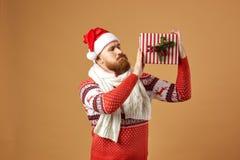 Homem ruivo com a barba vestida em uma camiseta vermelha e branca com cervos, em um lenço feito malha branco e em um chapéu de Sa fotografia de stock royalty free