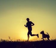 Homem running com suas silhuetas do por do sol do cão Fotografia de Stock Royalty Free