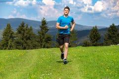 Homem Running da aptidão que sprinting fora na paisagem bonita imagem de stock