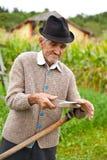 Homem rural idoso que usa o scythe imagens de stock