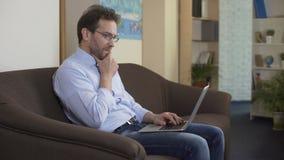 Homem sério com portátil que pensa como fazer o dinheiro extra, tecnologias modernas vídeos de arquivo