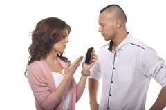 Homem sério que olha a mulher que aponta no telefone foto de stock royalty free