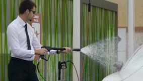 Homem sério que usa o equipamento profissional da lavagem de carros, polvilhando a água sobre o automóvel filme