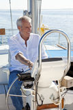 Homem sênior feliz na roda de um barco de vela Fotos de Stock Royalty Free