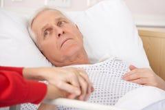 Homem sênior na mão da esposa da terra arrendada da cama de hospital imagens de stock