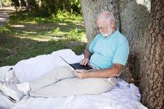 Homem sênior no parque com computador Fotografia de Stock Royalty Free