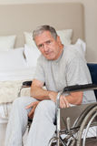 Homem sênior pensativo em sua cadeira de rodas Imagem de Stock