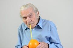 Homem sênior que bebe o sumo de laranja fresco Foto de Stock