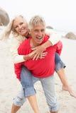 Homem sênior que dá o sobreposto da mulher na praia do inverno fotos de stock