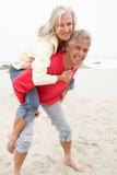 Homem sênior que dá o sobreposto da mulher na praia do inverno Fotografia de Stock