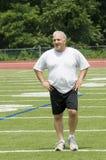 Homem sênior que estica exercitando o campo de esportes Imagem de Stock