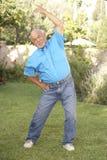 Homem sênior que exercita no jardim imagens de stock