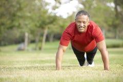 Homem sênior que exercita no parque Imagem de Stock