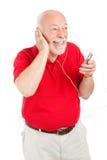 Homem sênior que joga MP3s Fotos de Stock Royalty Free