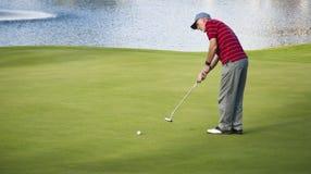 Homem sênior que joga o golfe por um lago foto de stock