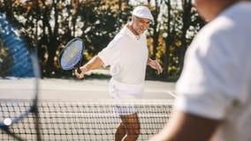 Homem sênior que joga o tênis foto de stock royalty free