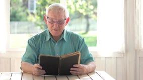 Homem sênior que lê um livro video estoque