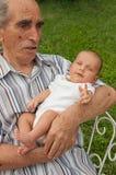 Homem sênior que prende seu Great-grandson Fotografia de Stock Royalty Free