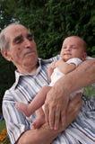 Homem sênior que prende seu Great-grandson Imagem de Stock