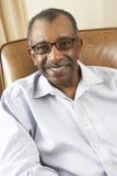Homem sênior que relaxa na cadeira em casa Fotografia de Stock Royalty Free