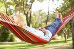 Homem sênior que relaxa no Hammock Foto de Stock