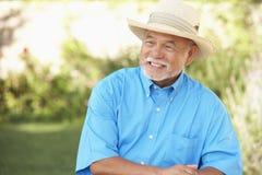 Homem sênior que relaxa no jardim fotografia de stock