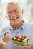 Homem sênior que sorri na câmera e que come a salada foto de stock