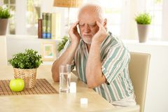 Homem sênior que tem a dor de cabeça Fotos de Stock Royalty Free