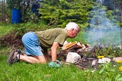 Homem sênior que tenta fazer uma fogueira Foto de Stock Royalty Free