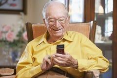 Homem sênior que texting no telefone móvel fotos de stock royalty free