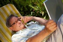 Homem sênior que usa o portátil ao ar livre Fotografia de Stock