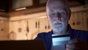 Homem sênior que usa o portátil em casa Pensionista que compra em linha com o cartão de crédito no computador na noite filme
