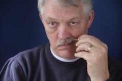 Homem sênior que usa o toothpick fotos de stock royalty free