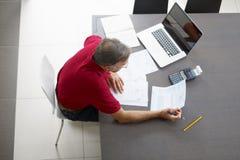 Homem sênior que verific para casa finanças Fotografia de Stock
