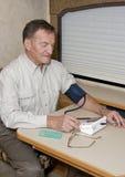 Homem sênior que verific a pressão sanguínea Imagens de Stock