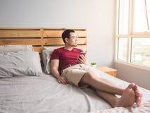 Homem só que joga seu telefone em seu quarto Imagem de Stock Royalty Free