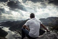 Homem só que olha com esperança no horizonte no pico de montanha com luz solar dramática durante o por do sol com efeito da luz n imagem de stock