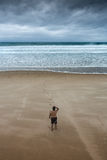 Homem só que olha fixamente na praia nublado imagem de stock