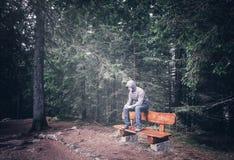 Homem só que senta-se no banco imagens de stock