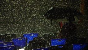 Homem só sob o guarda-chuva na chuva da noite filme