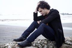 Homem só triste que senta-se na frente do oceano com as ondas no inverno Fotografia de Stock Royalty Free