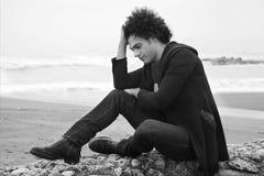Homem só triste que senta-se na frente do oceano com as ondas no retrato preto e branco do inverno Imagens de Stock Royalty Free