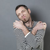 Homem 40s desapontado que cruza seus braços em ombros para expressar o pesar Fotos de Stock