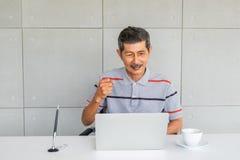 Homem s?nior asi?tico com roupa ocasional Exulte, levante o assistente do punho Olhar de assento à tela de laptop imagem de stock royalty free