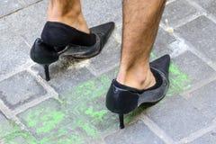 Homem sapatas vestindo dos saltos altos de um preto Imagem de Stock