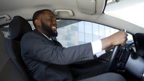 Homem satisfeito no terno de negócio que senta-se no carro, compra bem sucedida, felicidade fotografia de stock