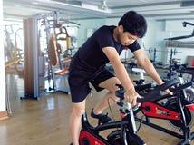 Homem saudável novo que exercita na máquina da bicicleta no gym do esporte Conceito da aptidão e do exercício imagem de stock